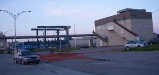 Ice plant with 300 ton travelift in background, guy repairing nets in parking lot!